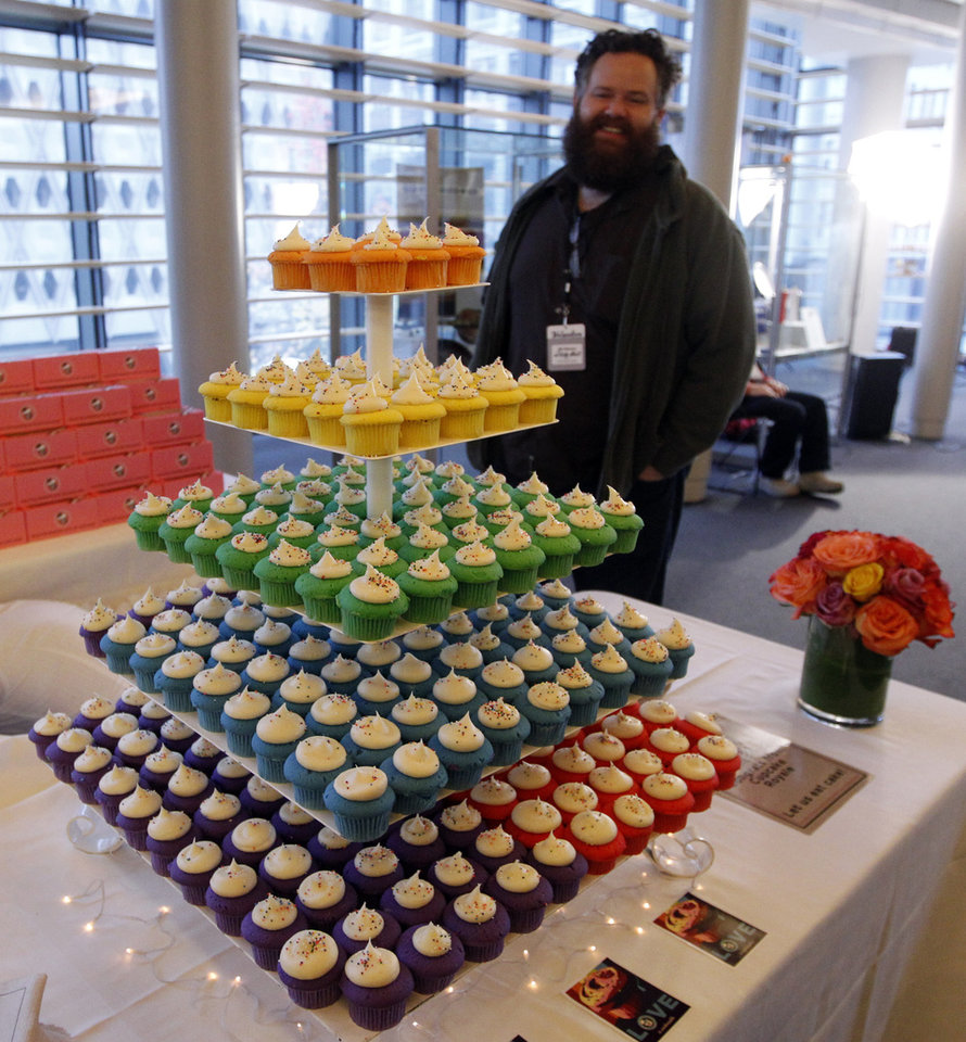 Photo - FILE - In this Dec. 9, 2012 file photo, a wedding cake made of rainbow-colored layers of cupcakes waits for newlyweds in a reception area at Seattle City Hall, where some of the first gay couples to legally wed in the state took their vows. On Tuesday, the US Supreme Court will begin hearing two days of cases involving gay marriage. (AP Photo/Elaine Thompson)