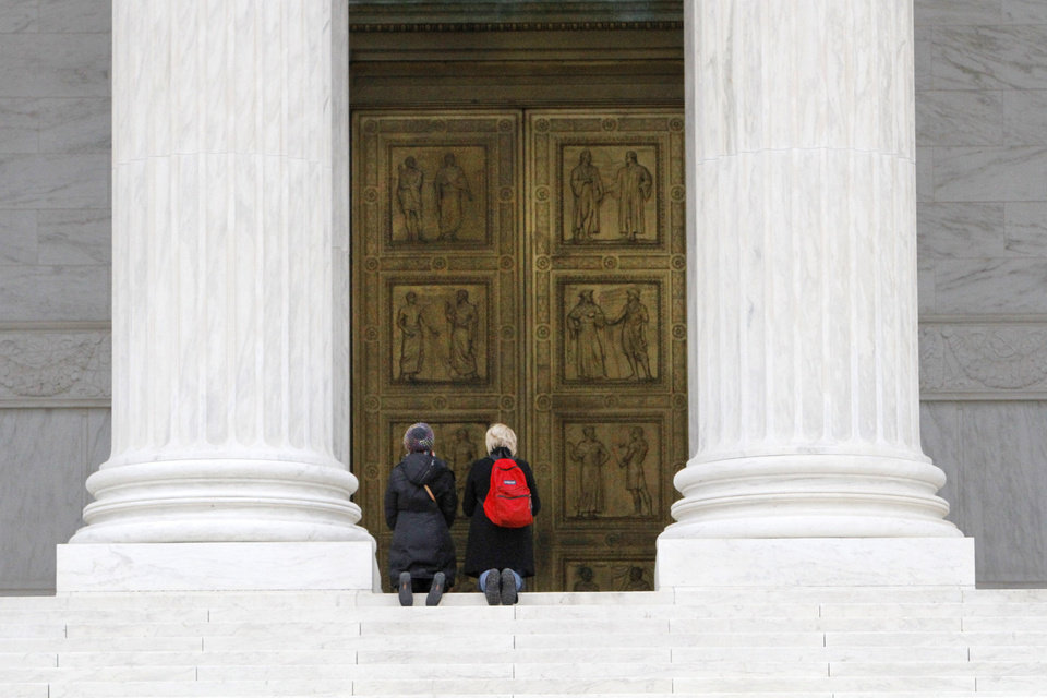 Two women kneel in prayer at the top of the U.S. Supreme Court steps in Washington, Sunday, Jan. 22, 2012. On Jan. 22, 1973, 39 years earlier, the court handed down its controversial Roe vs. Wade decision, which extended a woman's right to privacy to include the right to have an abortion. (AP Photo/Jacquelyn Martin)