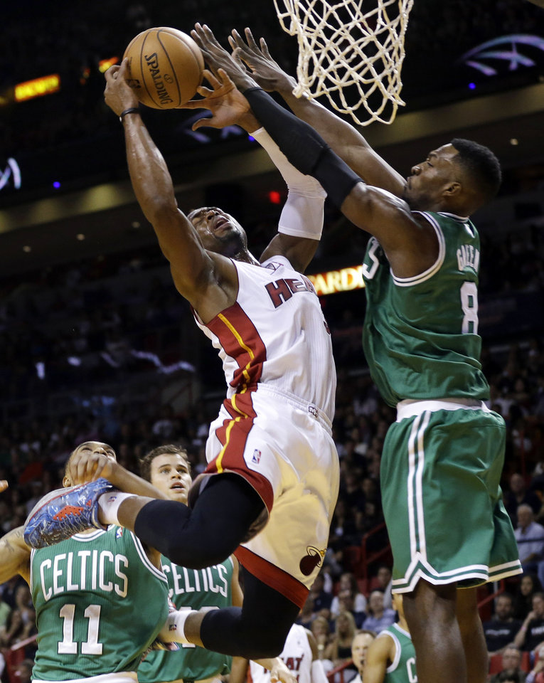 Photo - Miami Heat's Dwyane Wade, left, is fouled by Boston Celtics' Jeff Green (8) during the first half of an NBA basketball game Saturday, Nov. 9, 2013, in Miami. (AP Photo/Lynne Sladky)