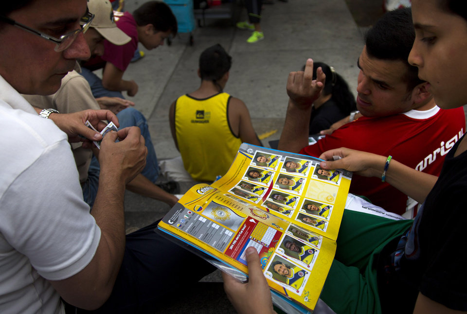 Photo - A boy searches for the sticker that he needs to complete his  World Cup sticker album at a meeting of collectors in Caracas, Venezuela, Saturday, June 21, 2014.  While soccer has long taken a backseat to baseball and even basketball in Venezuela, the ritual of sicker collection still sparks a frenzy. Traders say the hobby provides a connection to the tournament, and a distraction from the troubles that have recently wracked the country. (AP Photo/Ramon Espinosa)