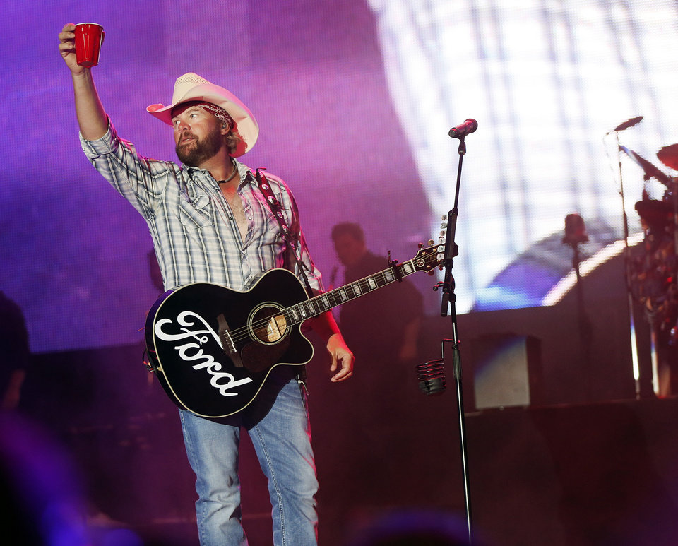 Photo - OKLAHOMA COUNTRY SINGER / SONGWRITER / MUSICIAN / PERFORMER / BENEFIT CONCERT / TORNADO AID: Toby Keith raises his red solo cup as he takes the stage during the Oklahoma Twister Relief Concert, benefiting victims of the May tornadoes, at Gaylord Family - Oklahoma Memorial Stadium on the campus of the University of Oklahoma in Norman, Okla., Saturday, July 6, 2013. Photo by Nate Billings, The Oklahoman