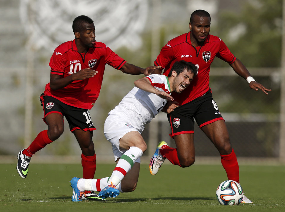 Photo - Iran's Khosrow Heidari, center, competes for the ball with Trinidad and Tobago's Kevin Molino, left, and Khaleem Hyland during the first half of an international soccer friendly at the Corinthians soccer team training center in Sao Paulo, Brazil, Sunday, June 8, 2014. Iran will play in group F of the 2014 soccer World Cup. (AP Photo/Julio Cortez)
