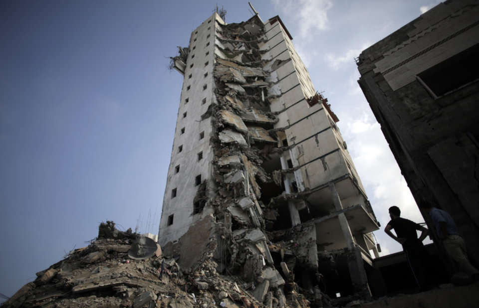 Photo - Palestinians inspect the damage to the Italian Complex following several late night Israeli airstrikes in Gaza City, Tuesday, Aug. 26, 2014. Israel bombed two Gaza City high-rises with dozens of homes and shops Tuesday, collapsing the 15-story Basha Tower and severely damaging the Italian Complex in a further escalation in seven weeks of cross-border fighting with Hamas. (AP Photo/Khalil Hamra)