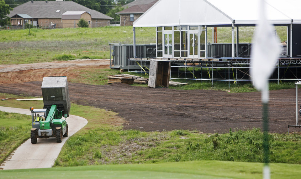 Photo - A construction worker drives a forklift of building material to help build temporary buildings that are being erected on the course at Oak Tree National Country Club in preparation for the 2014 U.S. Senior Open, held in July, on June 12, 2014. Photo by KT King/The Oklahoman