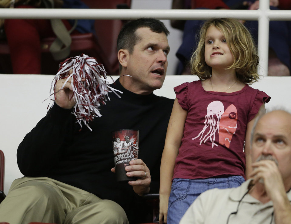 Photo - San Francisco 49ers head coach Jim Harbaugh sits with his 5-year-old daughter, Addison, during halftime of Stanford's NCAA college basketball game against Utah on Saturday, March 8, 2014, in Stanford, Calif. (AP Photo/Eric Risberg)