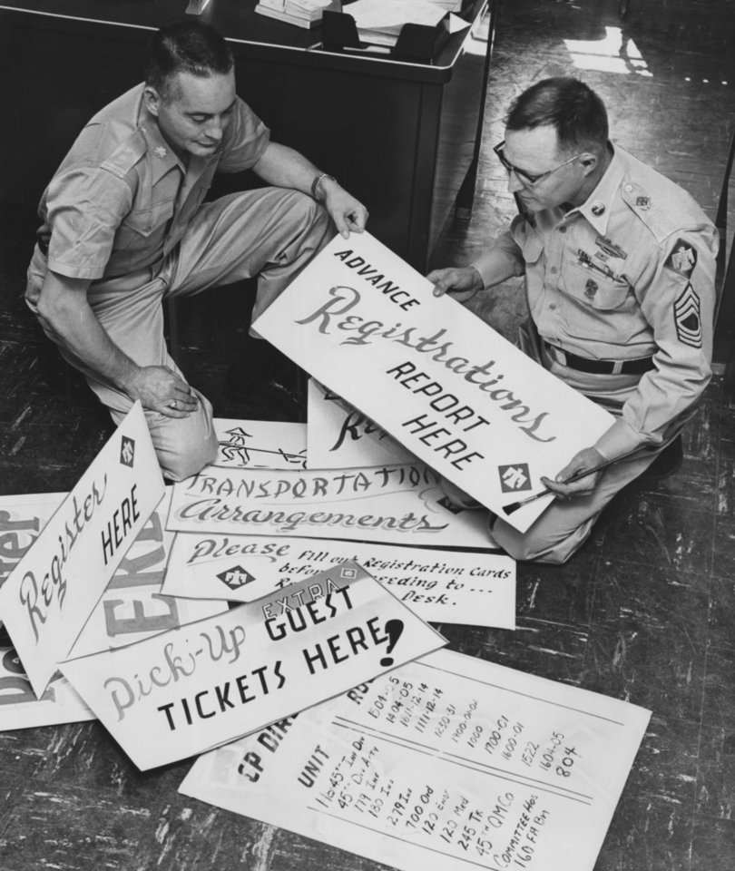 Photo - Directions aplenty will await Thunderbirds who come in for the annual reunion of the 45th Infantry Division Association Friday, Saturday and Sunday at the Skirvin Hotel, from registration to location of the various unit command posts for reunion with friends.  Maj. Harold Dallam, left, and M/Sgt. Jack Clapp, look at the signs here.  Clapp, who is handy with the brush for either signs or training aids, did the art work.  Staff photo by George Tapscott, and dated 10/16/1959.  Published in The Daily Oklahoman 10/26/1959.