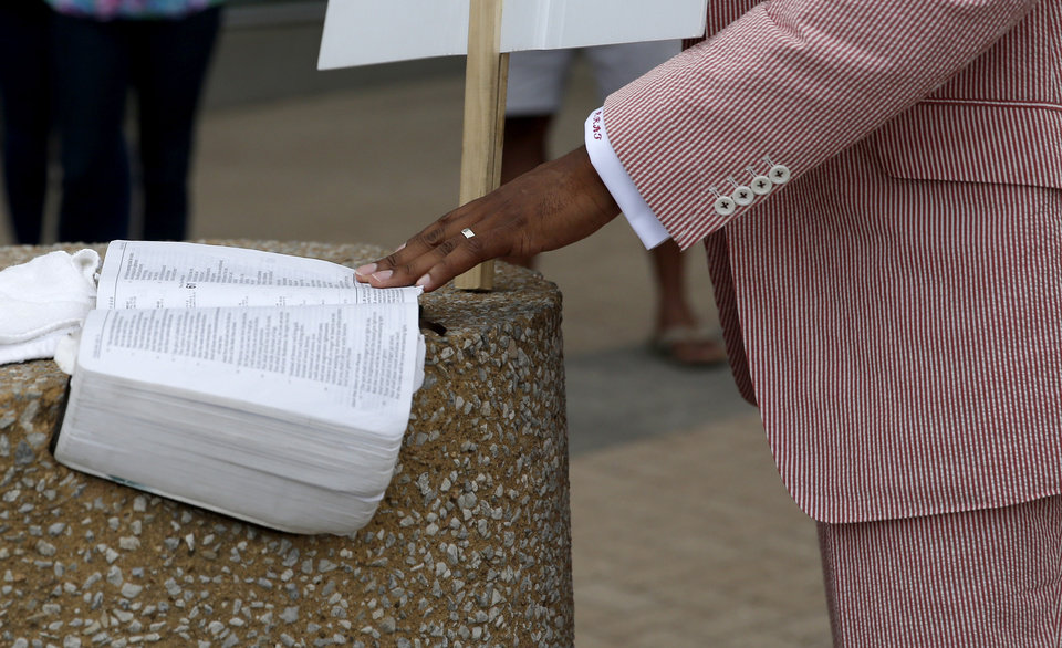 Photo - The Rev. Robert Turner reads from the Bible at Tulsa City Hall in Tulsa, Okla., Wednesday, July 29, 2020. Turner has protested for reparations for victims of the 1921 Tulsa Race Massacre each Wednesday at Tulsa City Hall. Photo by Sarah Phipps, The Oklahoman