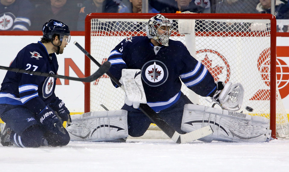 Photo - Tampa Bay Lightning's Ondrej Palat, not shown, scores on Winnipeg Jets goaltender Ondrej Pavelec (31) with Eric Tangradi (27) in the crease during the second period of an NHL hockey game Tuesday, Jan. 7, 2014, in Winnipeg, Manitoba. (AP Photo/The Canadian Press, Trevor Hagan)