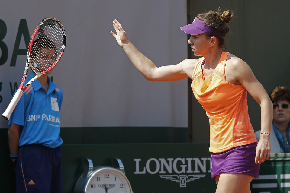 Photo - Romania's Simona Halep throws her racket away after missing a return during the third round match of the French Open tennis tournament against Spain's Maria-Teresa Torro-Flor at the Roland Garros stadium, in Paris, France, Saturday, May 31, 2014. (AP Photo/Michel Euler)