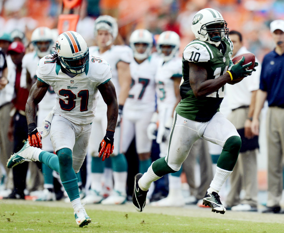Photo -   New York Jets wide receiver Santonio Holmes (10) runs with the ball as Miami Dolphins cornerback Richard Marshall (31) pursues in overtime of an NFL football game, Sunday, Sept. 23, 2012 in Miami. The Jets won 23-20. (AP Photo/Rhona Wise)