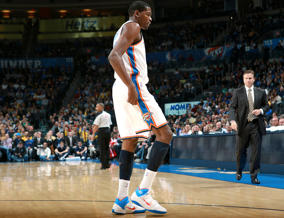 Photo - Oklahoma City's Kevin Durant limps on his right ankle following a collision in the first half against Houston during their NBA basketball game at the OKC Arena in downtown Oklahoma City on Wednesday, Nov. 17, 2010. Photo by John Clanton, The Oklahoman