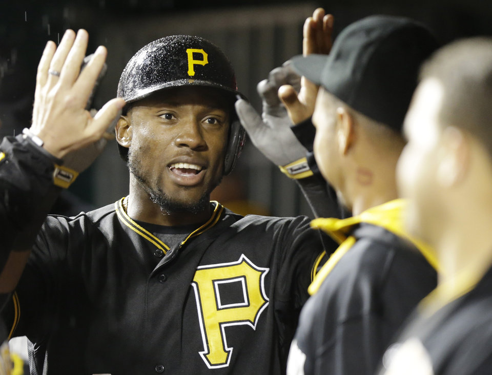 Photo - Pittsburgh Pirates' Starling Marte is congratulated after hitting a solo home run off Cincinnati Reds starting pitcher Homer Bailey in the fifth inning of a baseball game, Monday, April 14, 2014, in Cincinnati. (AP Photo/Al Behrman)