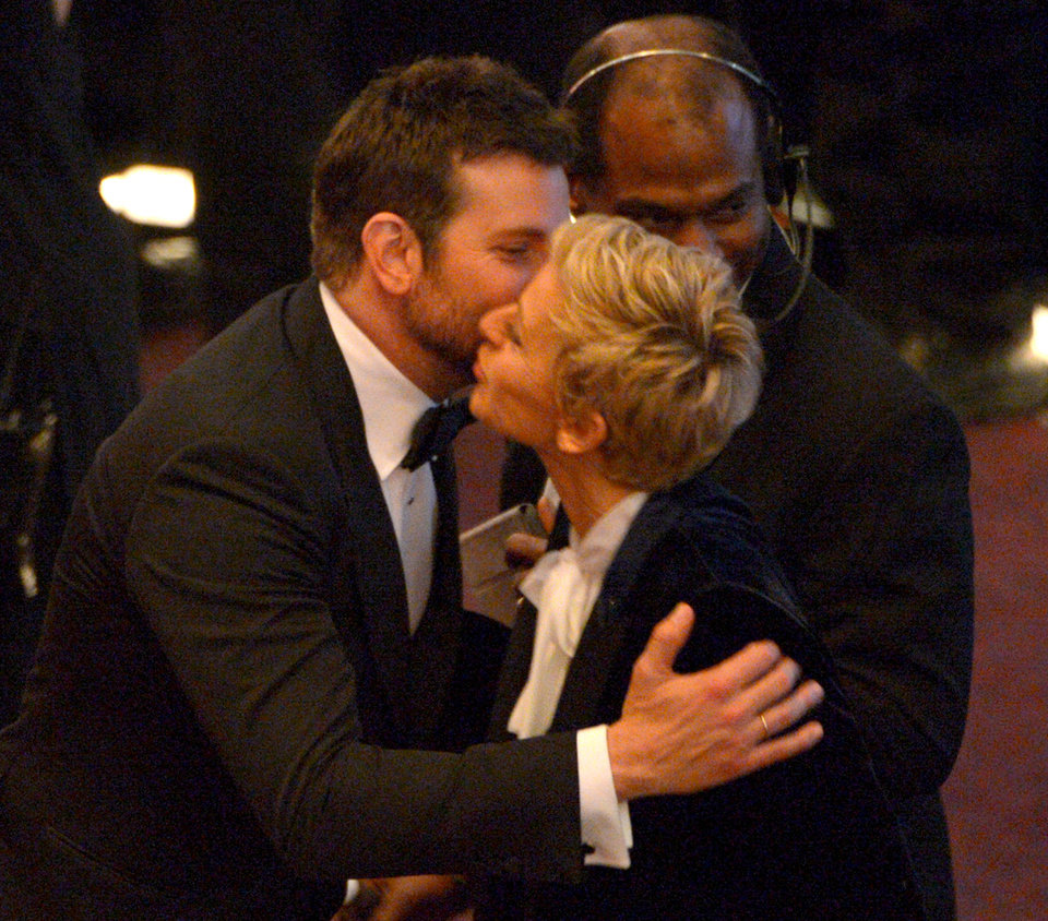 Photo - Bradley Cooper, left, and Ellen DeGeneres kiss in the audience during the Oscars at the Dolby Theatre on Sunday, March 2, 2014, in Los Angeles.  (Photo by John Shearer/Invision/AP)