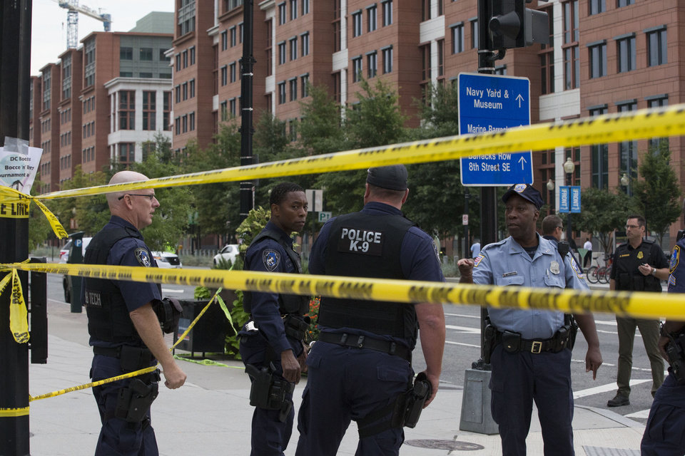 Photo - Police work the scene on M Street, SE in Washington near the Washington Navy Yard on Monday, Sept. 16, 2013. The U.S. Navy says one person is injured after a shooting at a Navy building in Washington. Police and emergency crews gathered Monday morning outside the Naval Sea Systems Command Headquarters building, where the shooting was reported.  (AP Photo/Jacquelyn Martin)