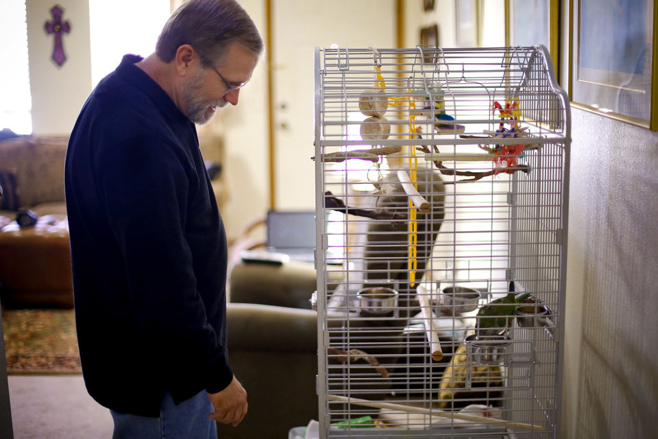 Photo - Alzheimers patient Ron Grant talks to his pet bird while at his home in Moore, Okla., Thursday, Dec. 12, 2013.  Grant was diagnosed in Oct. 2007, after noticing some lapses in his memory. Coming to peace with the outcome of his diagnosis, Grant says he does not want to live a long time with this. Grant's biggest concern is for his wife Vicky , 'If I live long enough for things to get bad, what will this do to her.' he says. Photo by Chris Landsberger, The Oklahoman
