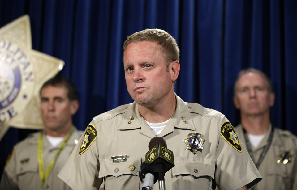 Photo - Las Vegas Assistant Sheriff Kevin McMahill, center, speaks during a news conference, Monday, June 9, 2014, in Las Vegas. Police say two police officers, along with a bystander, were killed by Jerad and Amanda Miller yesterday. (AP Photo/John Locher)