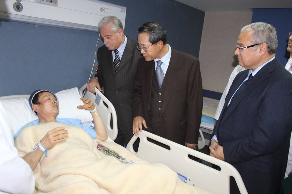 Photo - In this photo released by the office of the South Sinai governor, Egyptian Minister of Tourism Hesham Zazou, right, Deputy Chief of Mission of the South Korean Embassy in Egypt, Mr. Kwon Sae Young, second right, and South Sinai governor Major General Khaled Foda, visit a South Korean tourist who was injured during an explosion that targeted a tourist bus, as he received medical treatment in Sharm El-Sheik hospital, in Egypt, late Sunday, Feb. 16, 2014. An explosion ripped through a tourist bus near a border crossing between Egypt and Israel in the Sinai Peninsula, killing several South Koreans and the Egyptian driver, security officials said. (AP Photo/Office of the South Sinai governor)