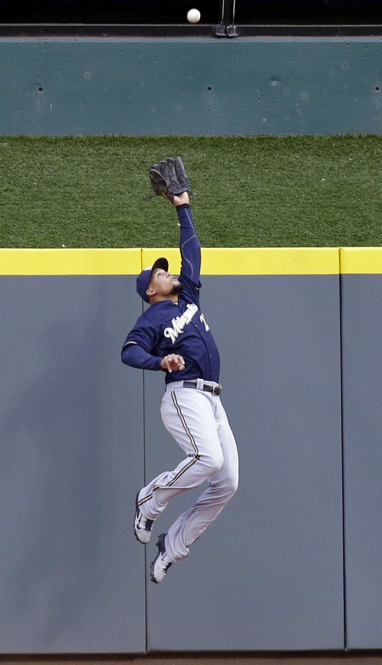Photo - Milwaukee Brewers center fielder Carlos Gomez catches a fly ball hit by Cincinnati Reds' Joey Votto in the first inning of a baseball game, Thursday, May 1, 2014, in Cincinnati. (AP Photo/Al Behrman)