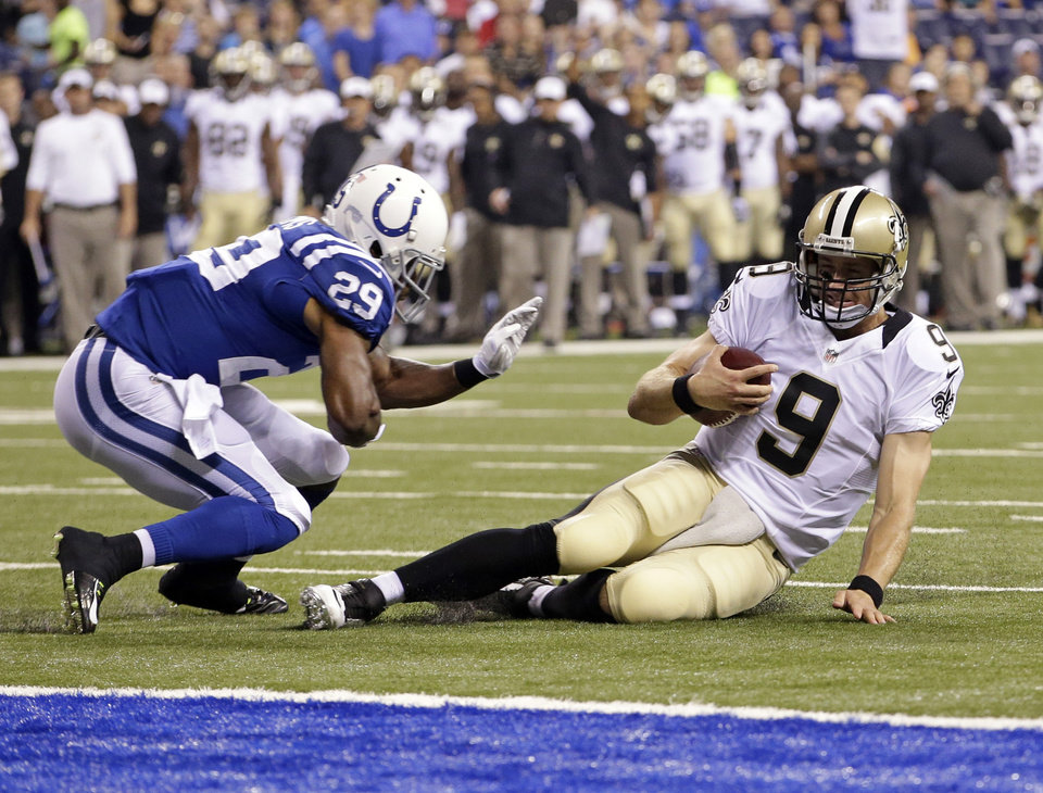 Photo - New Orleans Saints quarterback Drew Brees slides in under Indianapolis Colts defensive back Marcus Burley during the first half of an NFL preseason football game in Indianapolis, Saturday, Aug. 23, 2014. (AP Photo/AJ Mast)