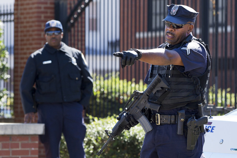 Photo - An armed officer who said he is with the Department of Defense, warns off a pedestrian to stay away from the gate at the Washington Navy Yard, closed to all but essential personnel, in Washington, on Tuesday, Sept. 17, 2013, the day after a gunman launched an attack inside the Washington Navy Yard on Monday, spraying gunfire on office workers in the cafeteria and in the hallways at the heavily secured military installation in the heart of the nation's capital. (AP Photo/Jacquelyn Martin)