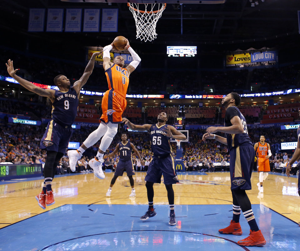 Photo - Oklahoma City's Russell Westbrook (0) goes up for a dunk in front of New Orleans' Terrence Jones (9), E'Twaun Moore (55) and Anthony Davis (23) during the NBA game between the Oklahoma City Thunder and the New Orleans Pelicans at the Chesapeake Energy Arena,  Sunday, Dec. 4, 2016. Photo by Sarah Phipps, The Oklahoman