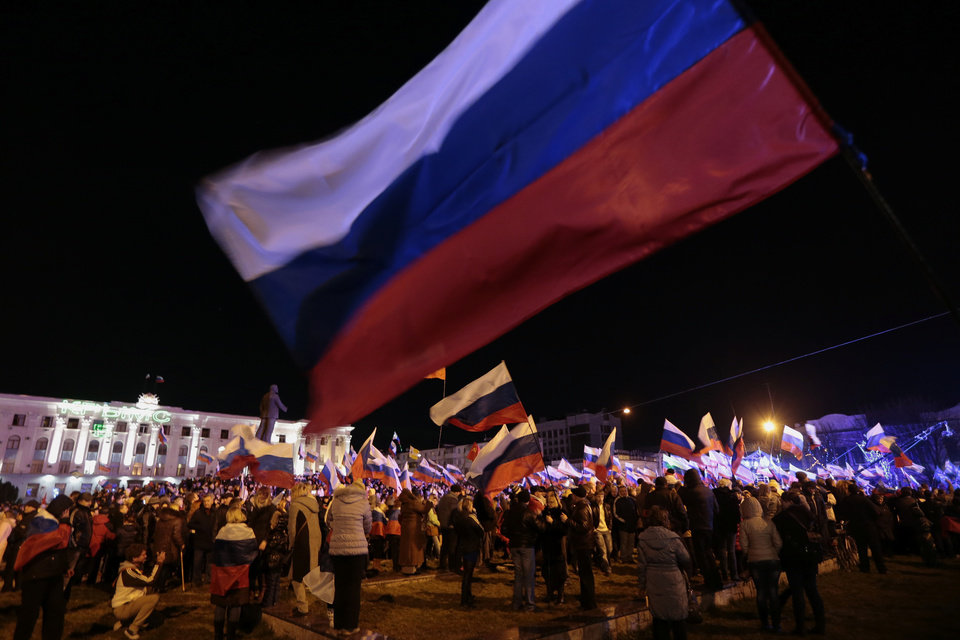 Photo - Pro-Russian people celebrate in Lenin Square, in Simferopol, Ukraine, Sunday, March 16, 2014. Fireworks exploded and Russian flags fluttered above jubilant crowds Sunday after residents in Crimea voted overwhelmingly to secede from Ukraine and join Russia. The United States and Europe condemned the ballot as illegal and destabilizing and were expected to slap sanctions against Russia for it. (AP Photo/Ivan Sekretarev)