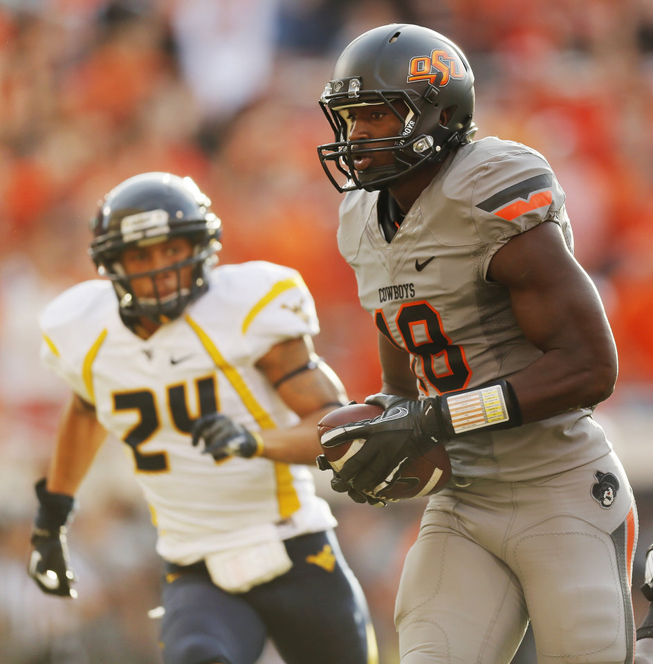 Oklahoma State\'s Blake Jackson (18) takes a reception for a touchdown past West Virginia\'s Cecil Level (24) in the second quarter during a college football game between Oklahoma State University (OSU) and West Virginia University (WVU) at Boone Pickens Stadium in Stillwater, Okla., Saturday, Nov. 10, 2012. Photo by Nate Billings, The Oklahoman