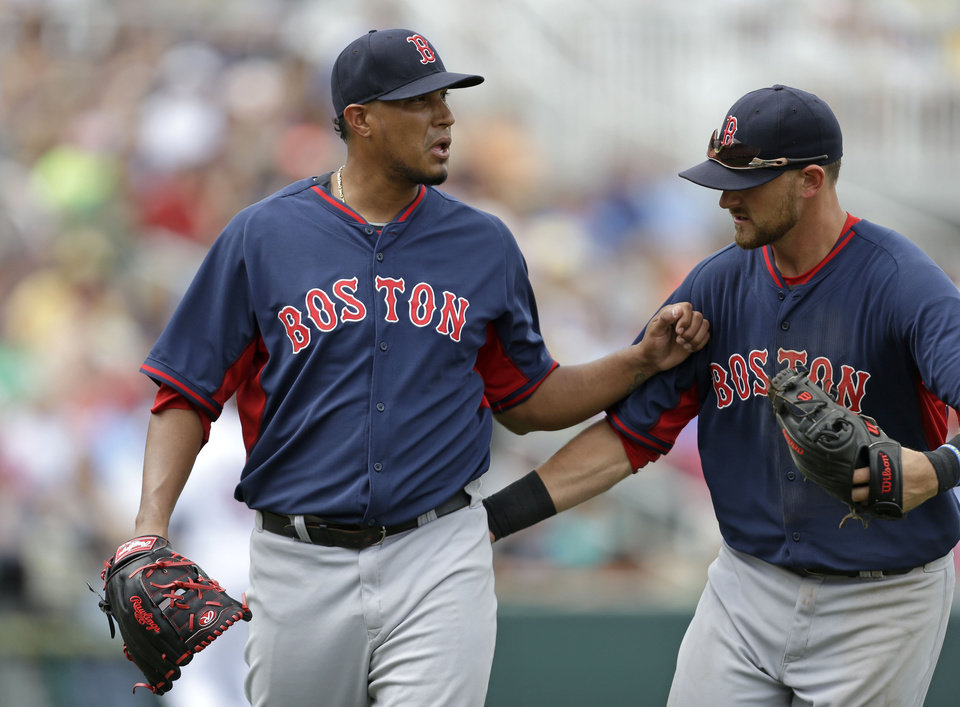 Photo - Boston Red Sox third baseman Will Middlebrooks, right, pats starting pitcher Felix Doubront (22) as he walks off the mound at the end of the fourth inning of an exhibition baseball game against the Minnesota Twins in Fort Myers, Fla., Friday, March 28, 2014. (AP Photo/Gerald Herbert)