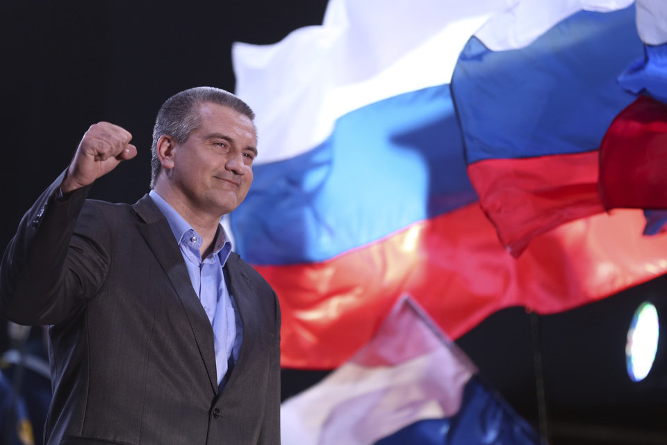 Photo - Crimea's Russia-backed leader Sergei Aksyonov gestures as people celebrate in Lenin Square, in downtown Simferopol, Ukraine, Sunday, March 16, 2014. Polls have closed in Crimea's contentious referendum on seceding from Ukraine and seeking annexation by Russia. The vote, unrecognized both by the Ukrainian government and the West, was held Sunday as Russian flags fluttered in the breeze and retirees grew weepy at the thought of reuniting with Russia. (AP Photo/Max Vetrov)