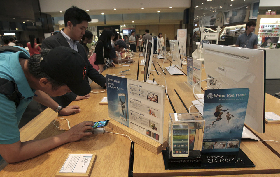 Photo - Visitors try out Samsung Electronics Co.'s Galaxy 5 at the company's showroom in Seoul, South Korea, Tuesday, July 8, 2014. Samsung Electronics Co. said operating profit declined to a two-year low in the second quarter, hit by the strong local currency and slowing demand for smartphones in China. (AP Photo/Ahn Young-joon)