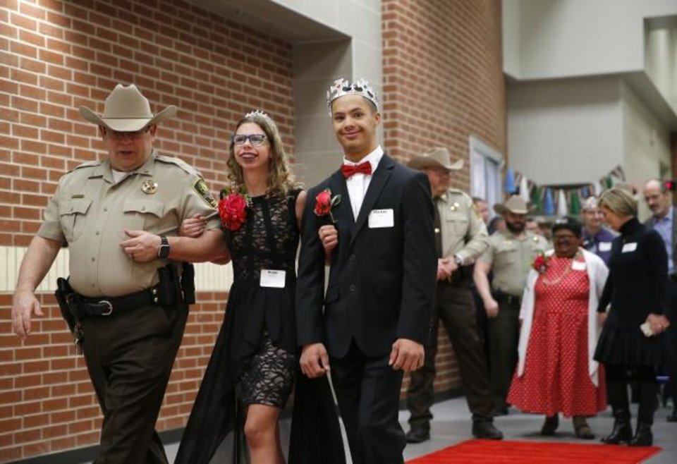 Photo -  Hope Hansen and Markus Lanier are escorted down the the red carpet by a Canadian County Sheriff deputy during the 2019 Night to Shine at Lincoln Learning Center in El Reno. [Sarah Phipps/The Oklahoman Archives]