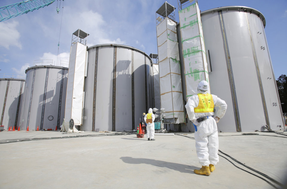 Photo - A worker in a protective suit and a mask looks at tanks, under construction, to store radioactive water, in the J1 area at the Tokyo Electric Power Co's (TEPCO) tsunami-crippled Fukushima Dai-ichi nuclear power plant in Okuma, Fukushima prefecture, northeastern Japan, Monday, March 10, 2014. (AP Photo/Toru Hanai, Pool)