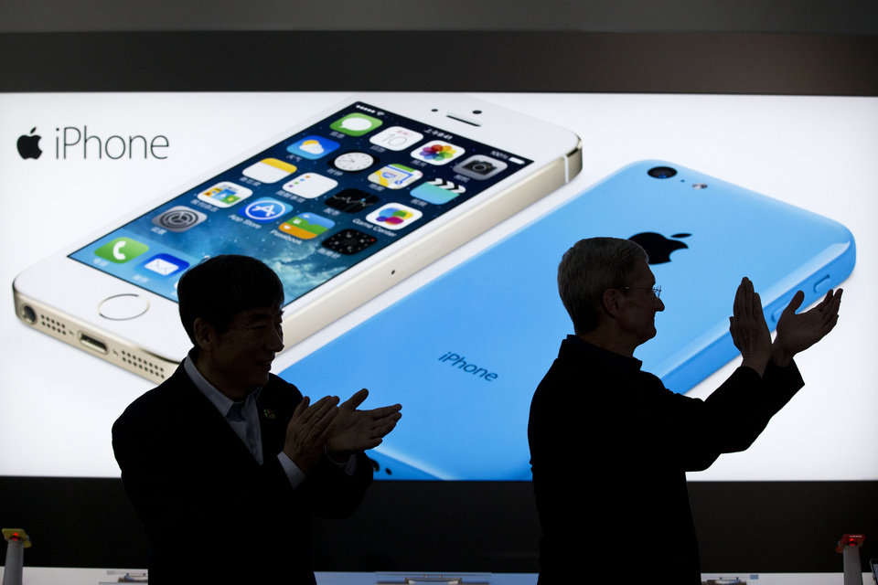 Photo - FILE - In this Jan. 17, 2014 file photo, Apple CEO Tim Cook, right, and China Mobile's chairman Xi Guohua are silhouetted against a screen showing iPhone products as they applaud during a promotional event that marks the opening day of sales of China Mobile's 4G iPhone 5s and iPhone 5c at a shop of the world's largest mobile phone operator in Beijing, China. The high-stakes battle between the world's largest smartphone makers is scheduled to wrap up this week after a monthlong trial that has pulled the curtain back on just how very cutthroat the competition is between Apple and Samsung. Closing arguments in the patent-infringement case are scheduled to begin Monday, April 28 with the two tech giants accusing each other, once again, of ripping off designs and features. At stake: $2 billion if Samsung loses, a few hundred million if Apple loses. (AP Photo/Alexander F. Yuan, File)