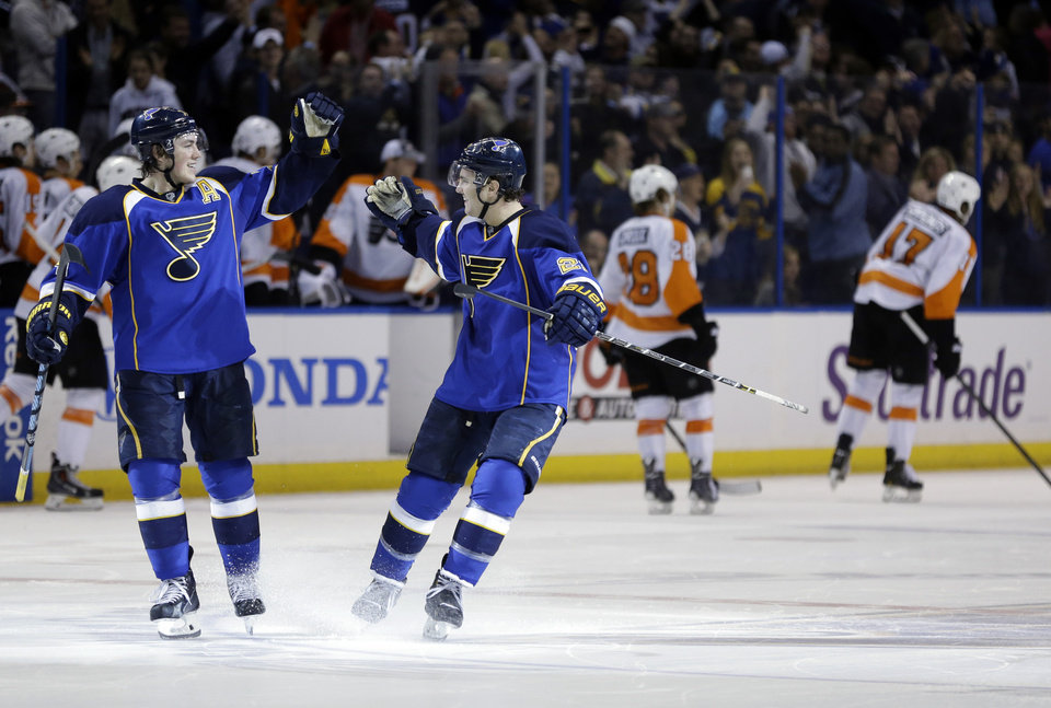 Photo - St. Louis Blues' Kevin Shattenkirk, second from left, is congratulated by teammate T.J. Oshie, left, after scoring the game-winning goal during a shootout of an NHL hockey game as Philadelphia Flyers' Claude Giroux and Wayne Simmonds, right, skate in the background Tuesday, April 1, 2014, in St. Louis. The Blues won 1-0. (AP Photo/Jeff Roberson)