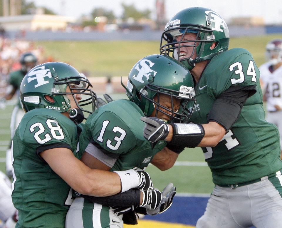 Photo - Edmond Santa Fe's  Taylor Ashcraft (28), Daniel Bly (13) and Conner Bays celebrate a touchdown during the high school football game between Edmond Santa Fe and Edmond Memorial at Wantland Stadium in Edmond, Okla.,  Friday, Sept. 2, 2011. Photo by Sarah Phipps, The Oklahoman