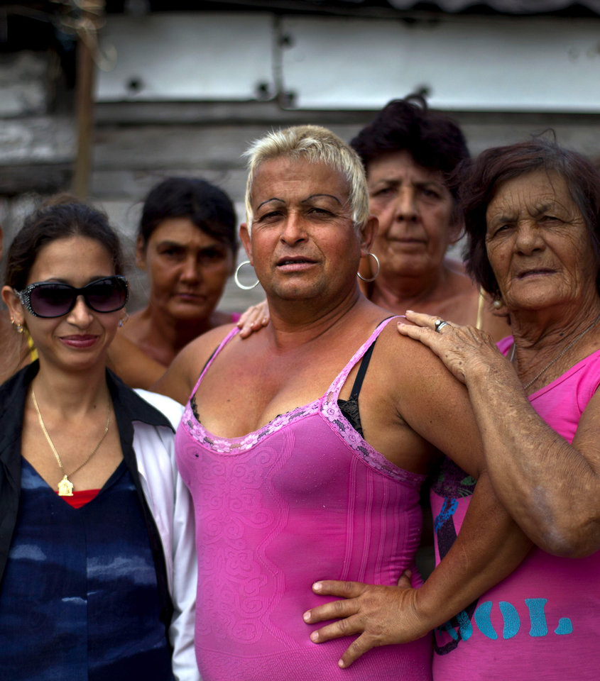 Adela Hernandez, 48, center, poses with her neighbors in the village of Caibarien, Cuba, Friday, Nov. 16, 2012. Hernandez, a biologically male Cuban who has lived as a female since childhood, served two years in prison in the 1980s for