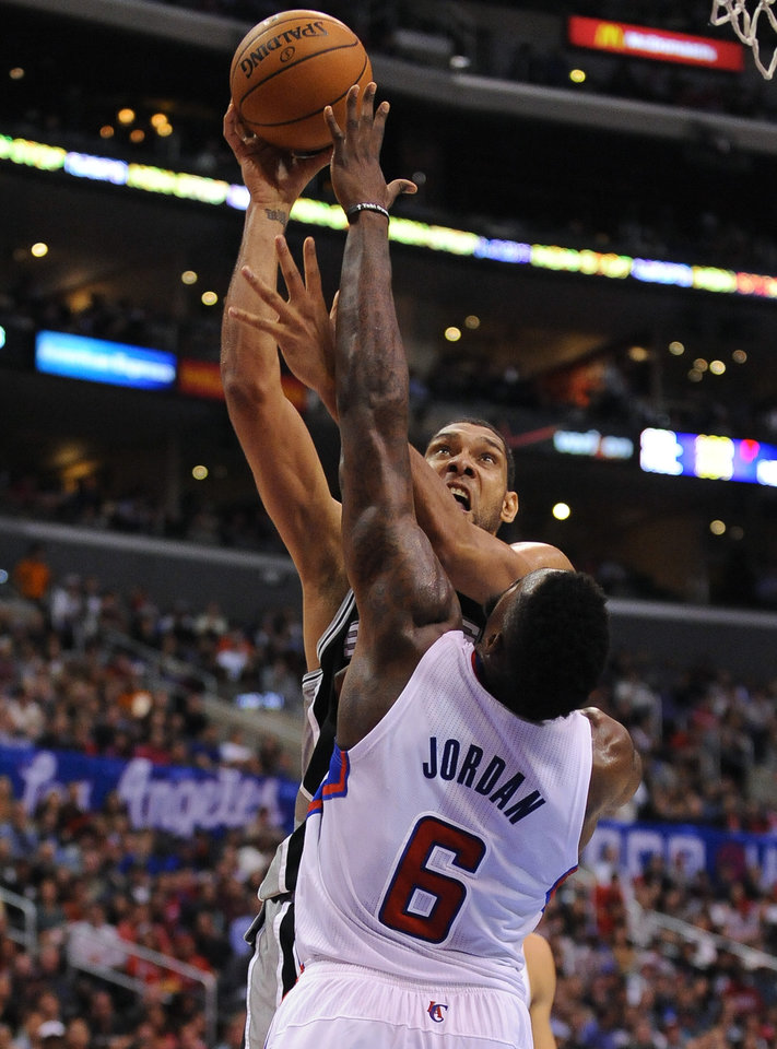 Photo - San Antonio Spurs forward Tim Duncan, back center, battles Los Angeles Clippers center DeAndre Jordan (6) as he makes a basket in the first half of a NBA basketball game, Tuesday, Feb. 18, 2014, in Los Angeles.(AP Photo/Gus Ruelas)