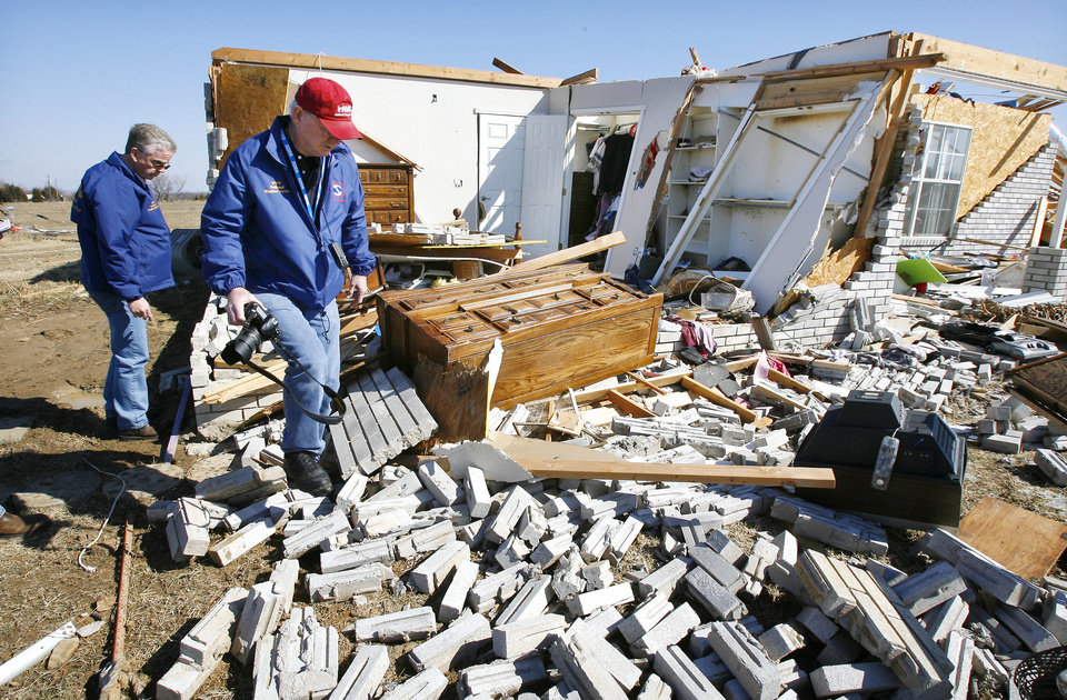 Photo - Rick Smith, warning coordination meteorologist, left, and Mike Foster, meteorologist in charge, both with the National Weather Service, Norman Forecast Office, are shown looking at tornado damage at Lone Grove in February 2009.  PAUL B. SOUTHERLAND - PAUL B. SOUTHERLAND, ARCHIVE PHO