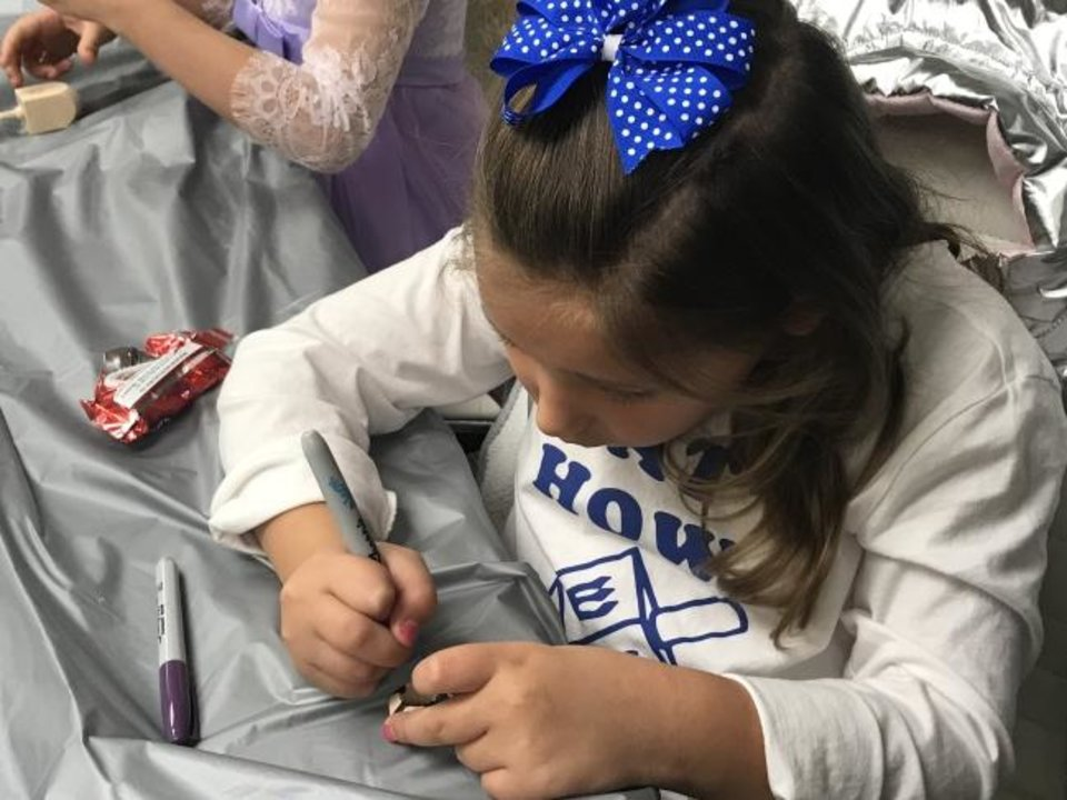 Photo -  Ally Lewis, 6, decorates her dreidel during a Hanukkah-themed session of PJ Library hosted by the Jewish Federation of Greater Oklahoma City. [Carla Hinton/The Oklahoman]