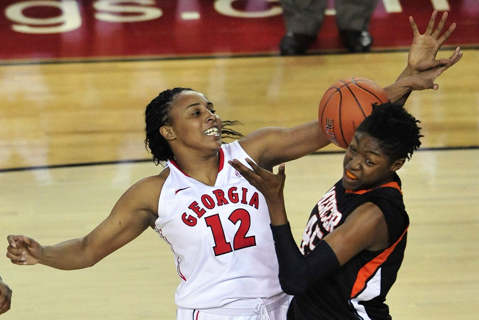 Georgia forward Jasmine Hassell (12) collides with Mercer center Teanna Robinson (45) as they compete for a rebound during the first half of an NCAA college basketball game, Tuesday, Dec. 4, 2012, in Athens, Ga. (AP Photo/Richard Hamm)