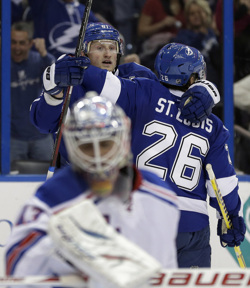 Tampa Bay Lightning center Steven Stamkos (91) celebrates with teammate right wing Martin St. Louis (26) after scoring against the New York Rangers during the second period of an NHL hockey game on Saturday, Feb. 2, 2013, in Tampa, Fla. (AP Photo/Chris O'Meara)