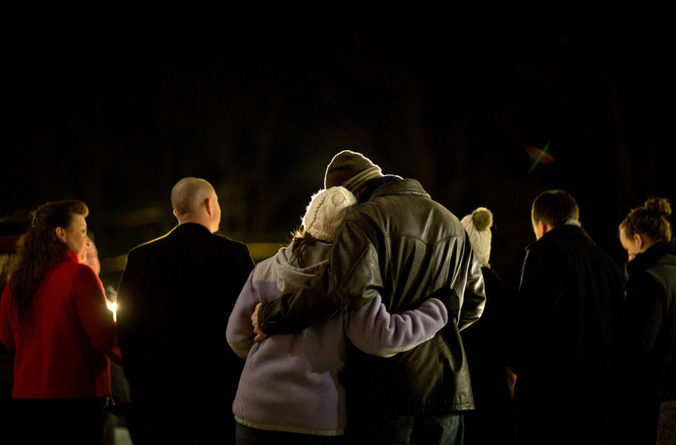 Photo - Brian Tenenhaus, right, comforts Lauren Foster, during a candlelight vigil outside the Edmond Town Hall, Saturday, Dec. 15, 2012, in Newtown, Conn.  A gunman walked into Sandy Hook Elementary School in Newtown Friday and opened fire, killing 26 people, including 20 children. (AP Photo/David Goldman) ORG XMIT: CTDG153