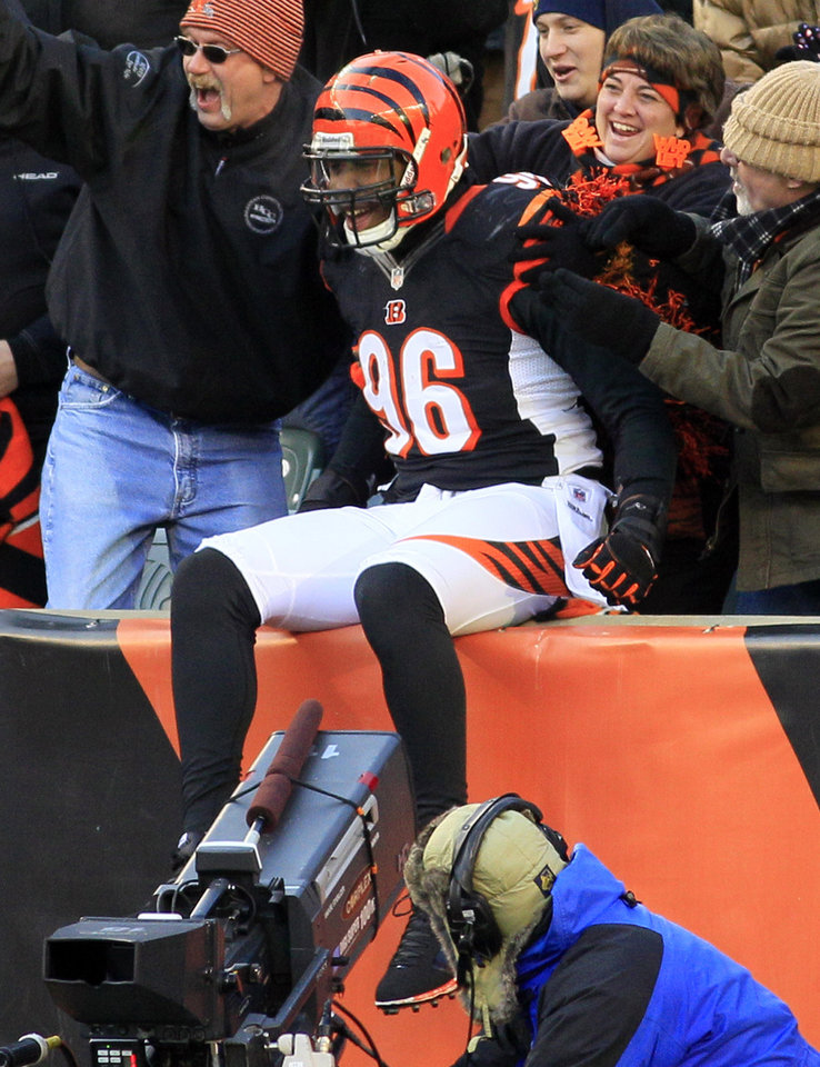 Photo - Cincinnati Bengals defensive end Carlos Dunlap (96) celebrates with fans after scoring a touchdown on an interception against the Baltimore Ravens in the second half of an NFL football game, Sunday, Dec. 30, 2012, in Cincinnati. (AP Photo/Tom Uhlman)