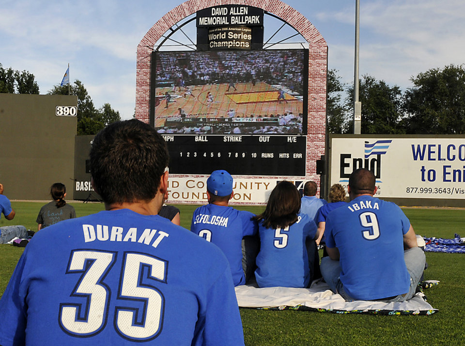 Oklahoma City Thunder fans sit in the outfield of David Allen Memorial Ballpark to watch a broadcast of Game 3 of the NBA Finals basketball series between the Thunder and the Miami Heat, Sunday, June 17, 2012, in Enid, Okla. Photo by Billy Hefton/Enid News & Eagle