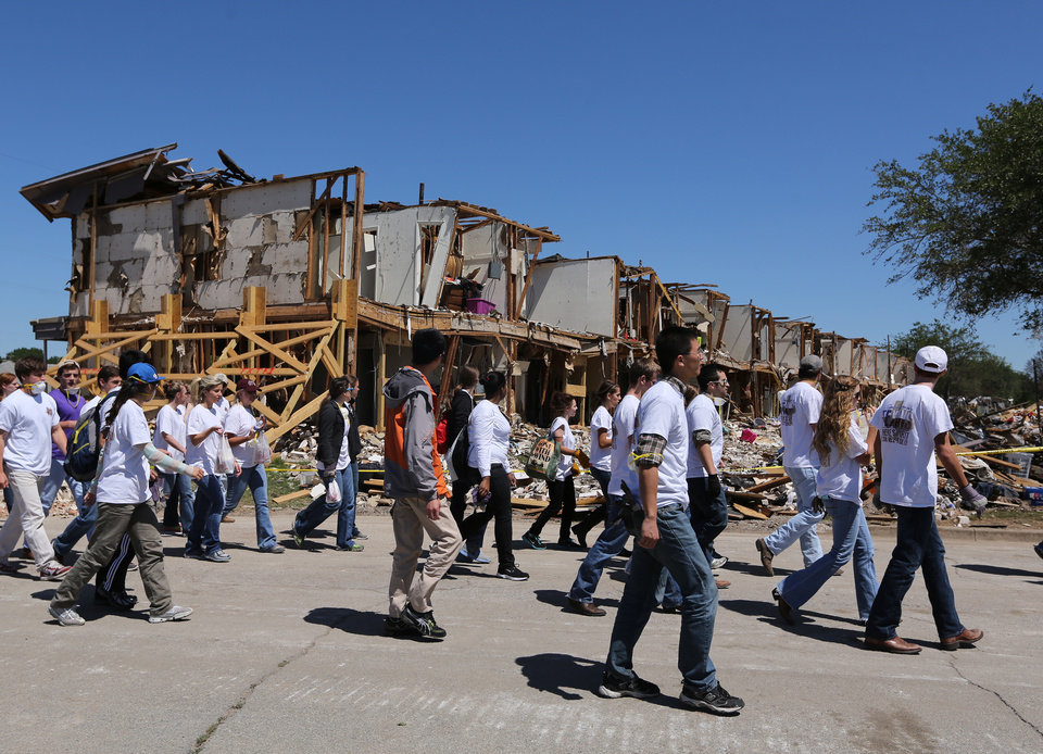 Photo - Texas A&M students walk past an apartment complex in West, Texas, Saturday, May 4, 2013, that was damaged due to the explosion at a fertilizer plant on April 17. The plant that exploded, killing 14 people, injuring more than 200 others and causing tens of millions of dollars in damage to the surrounding area, had only $1 million in liability coverage, lawyers said Saturday. (AP Photo/Waco Tribune Herald, Rod Aydelotte)