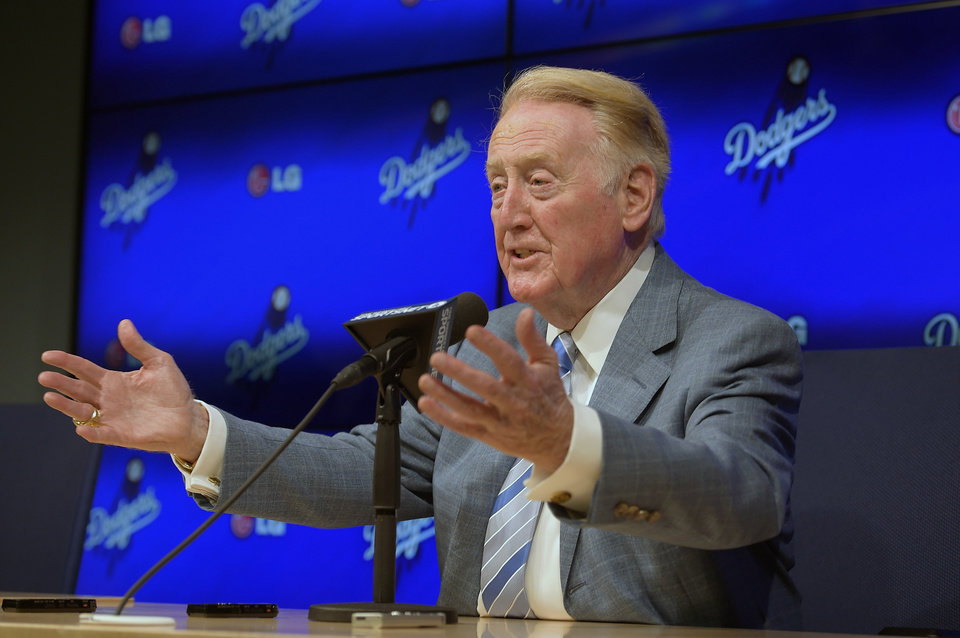 Photo - Los Angeles Dodgers announcer Vin Scully speaks to the media prior to a baseball game against the Atlanta Braves, Wednesday, July 30, 2014, in Los Angeles. The 86-year-old Hall of Fame announcer said Tuesday that he will return for his record 66th season with the team in 2015. (AP Photo/Mark J. Terrill)