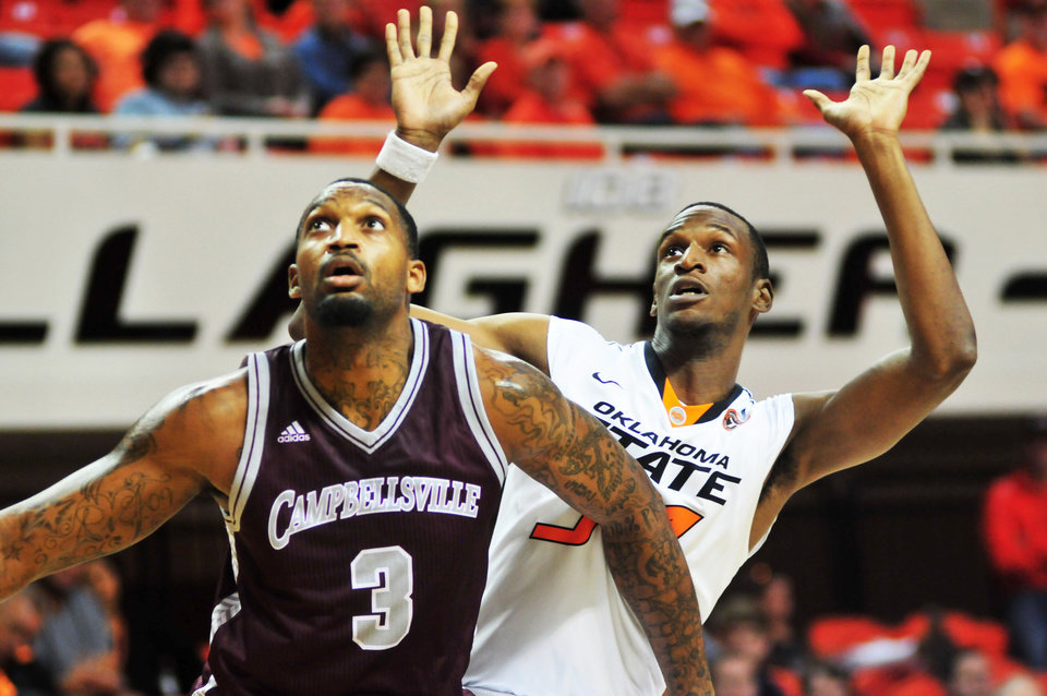 Oklahoma State forward Gary Gaskins (right) blocks out Campbellsville forward A'Darius Pegues during Oklahoma State's exhibition game versus Campbellsville on Oct. 27, 2013 at Gallagher Iba Arena in Stillwater, Okla. The Cowboys won 80-70, lead by Markel Brown's 13 points. Photo by KT King/For the Oklahoman
