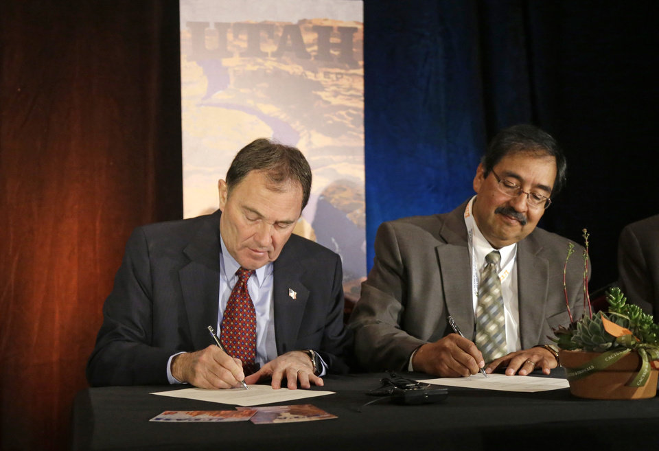 Photo - Utah Gov. Gary Herbert, left, kicks off his first annual Outdoor Recreation Summit by signing a long-awaited swap of state and federal lands in Grand, San Juan and Uintah Counties, with state Bureau of Land Management Director Juan Palma, right, Thursday, May 8, 2014, in Salt Lake City. The deal gives the federal government about 25,000 acres of conservation and recreation lands in exchange for about 35,000 acres of energy-rich land for the state.  (AP Photo/Rick Bowmer)
