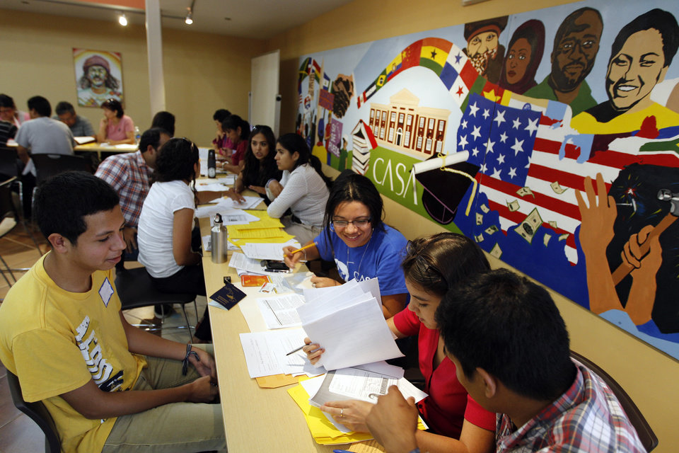 Photo -   Immigrant Angel Eduardo Aguiluz, left, from Honduras, get help with documents and filling for the Deferred Action Childhood Arrivals applications at Casa de Maryland in Langley Park, Md., on Wednesday Aug. 15, 2012. Thousands of young illegal immigrants lined up hoping for the right to work legally in America without being deported. The Obama administration's Deferred Action for Childhood Arrivals could expand the rights of more than 1 million young illegal immigrants by giving them work permits, though they would not obtain legal residency here or a path to citizenship. (AP Photo/Jose Luis Magana)