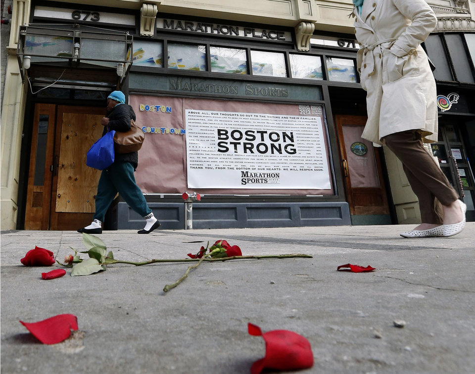 Photo - Pedestrians pass the spot where the first bomb detonated on Boylston Street near the finish line of the Boston Marathon Wednesday, April 24, 2013, in Boston. Traffic was allowed to flow all the way down Boylston Street on Wednesday morning for the first time since two explosions killed 3 people and injured many on April 15. (AP Photo/Michael Dwyer)
